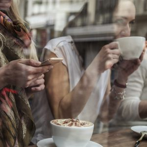 Friends enjoy together an hot coffee cup in a bar in Copenhagen. Close up on the women hands using mobile phones.